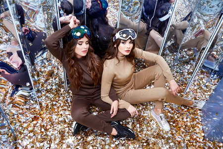 Two beautiful woman friends sit on the floor mirror sequins party fun celebrate new year holiday wear casual knitted wool suit ski goggles sport shoes extreme winter game brunette hair heath lifestyle.