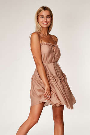 Beautiful woman fashion model makeup blond hair perfect body shape tanned skin wear clothes summer collection organic short beige silk dress stylish sandals shoes, accessory jewelry earrings date.