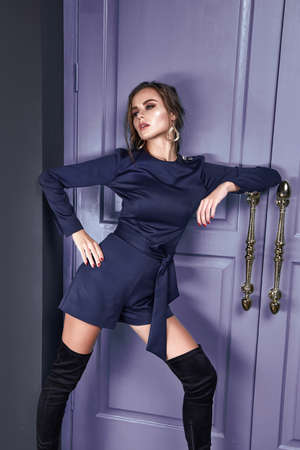 Beautiful sexy lady brunet hair spring autumn collection fashion clothes for date party success business woman wear short dark blue sit on the sofa room interior blue door luxury style accessory. Stock fotó