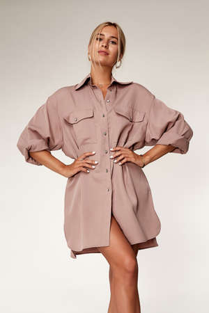 Beautiful sexy elegance woman skin tan body fashion model glamor pose wear trend casual clothes party summer pink long shirt dress collection makeup hair style blond success accessory studio.
