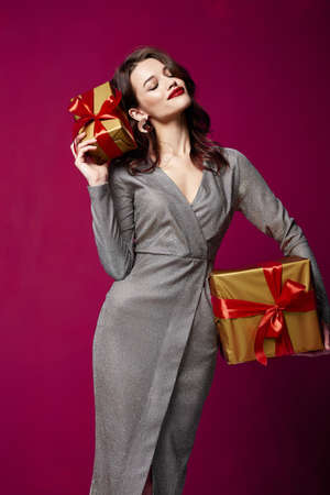 Beautiful sexy young brunette woman hair bright evening make-up red lips long fluffy eyelashes hold gift box holiday New Year joy fun happy merry Christmas Eve party celebration St. Valentine's Day. Stock fotó