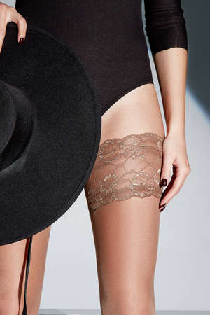 Part of woman body perfect shape hips legs skin tan wear stockings, nylons, pantyhose lingerie hosiery hose studio shot. on white background hat lace romantic.