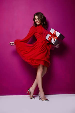 Beautiful young sexy woman thin slim figure evening makeup fashionable stylish dress clothing collection, brunette, gifts boxes red silk bows holiday party birthday New Year Christmas Valentine's Day. Stock fotó