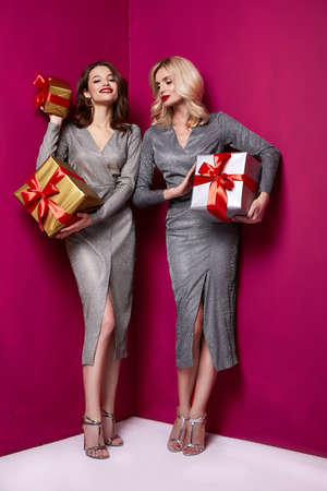 Two beautiful sexy young woman bright evening make-up red lips long fluffy eyelashes hold gift box holiday New Year joy fun happy merry Christmas Eve party celebration St. Valentine's Day girlfriend. Stock fotó