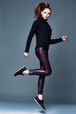 Beautiful sexy pretty woman perfect body shape face makeup wear black wool cashmere sweater and skinny lather pants sport shoes accessory casual clothes for party walk brunette hair fashion style.