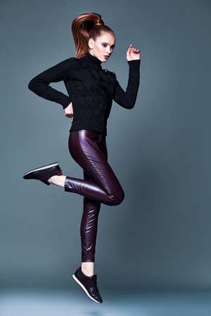 Beautiful pretty woman perfect body shape face makeup wear black wool cashmere sweater and skinny lather pants sport shoes accessory casual clothes for party walk brunette hair fashion style.