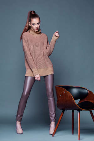 Beautiful woman sexy perfect body shape pretty face makeup wear beige wool cashmere sweater and skinny lather pants shoes accessory casual clothes for party brunette hair fashion model pose style. Stock fotó - 156175428