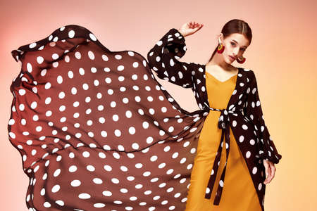 Glamor fashion woman long brunette hair natural evening makeup wear sexy silk long dress polka dot and red stylish from new catalog spring summer collection accessory jewelry earring body shape care.