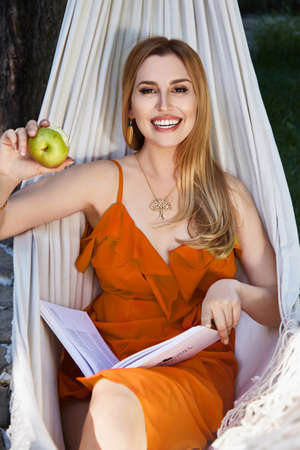 Beautiful woman model with long blond hair lies in a hammock relax rest exhale dressed in red silk dress reads interesting book eating apple in the garden organic food summer weather perfect weekend.