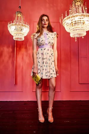 Sexy pretty beautiful woman long blond makeup red lips hair wear silk short dress casual style clothes for party fashion model pose accessory hand bag interior design room pink wall chandelier shine.