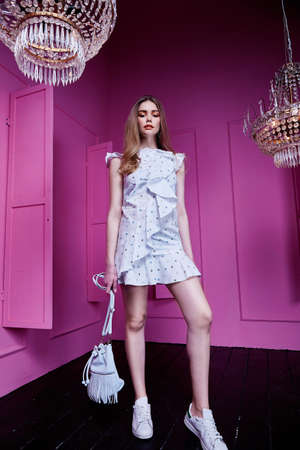 Beautiful sexy pretty woman long blond hair wear casual style clothes for party fashion model pose accessory hand bag interior design room pink wall chandelier shine. Stock fotó - 156175630
