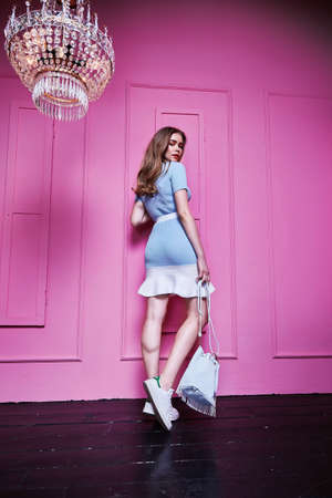 Interior design room pink wall crystal chandelier beautiful sexy pretty woman long blond hair fashion glamor model pose wear dress blue color casual style clothes party accessory hand bag elegant. Stock fotó