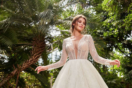 Beautiful woman bride fashion model brunette hair bright makeup pretty wear long silk white dress with lace bridal ceremony wedding espousal in blooming romance garden party marriage happy big day. 版權商用圖片 - 159922715