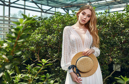 Beautiful woman bride fashion model blond hair bright makeup pretty wear long silk white dress lace bridal ceremony wedding espousal in blooming romance garden party marriage accessory hat. 版權商用圖片 - 159922716