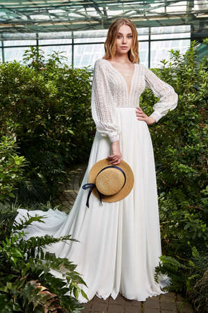 Beautiful woman bride fashion model blond hair bright makeup pretty wear long silk white dress lace bridal ceremony wedding espousal in blooming romance garden party marriage accessory hat. 版權商用圖片 - 159922721