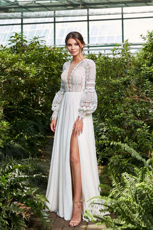 Beautiful woman bride fashion model brunette hair bright makeup pretty wear long silk white dress with lace bridal ceremony wedding espousal in blooming romance garden party marriage happy big day. 版權商用圖片