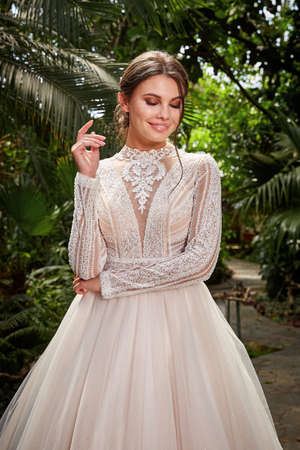 Beautiful woman bride fashion model brunette hair bright makeup pretty wear long silk white dress with lace bridal ceremony wedding espousal in blooming romance garden party marriage happy big day. 版權商用圖片 - 159922733
