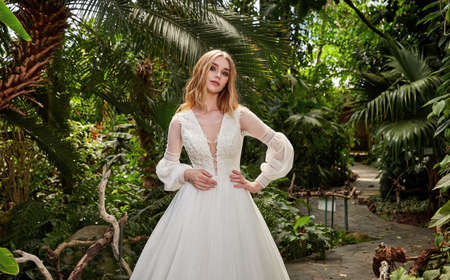Beautiful woman bride fashion model blond hair bright makeup pretty wear long silk white dress with lace bridal ceremony wedding espousal in blooming romance garden party marriage happy big day. 版權商用圖片