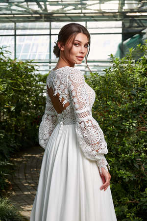 Sexy beautiful woman pretty bride wedding big day marriage ceremony in summer garden wearing long silk and lace white dress bright makeup hairstyle pure love. 版權商用圖片 - 159922973