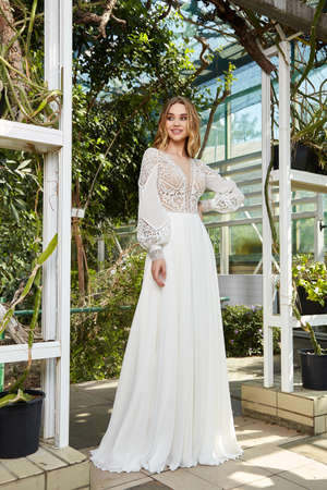 Beautiful woman model bride wearing white long silk and lace wedding dress fashion espousal bright makeup blond hairstyle ceremony in green summer garden love.