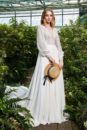 Beautiful woman bride fashion model blond hair bright makeup pretty wear long silk white dress lace bridal ceremony wedding espousal in blooming romance garden party marriage accessory hat. 版權商用圖片 - 161473923