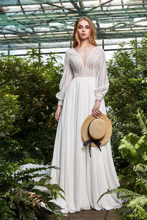 Beautiful woman bride fashion model blond hair bright makeup pretty wear long silk white dress lace bridal ceremony wedding espousal in blooming romance garden party marriage accessory hat.