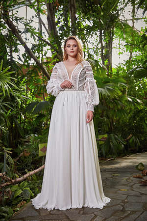 Beautiful sexy woman model bride wearing white long silk and lace wedding dress fashion espousal bright makeup hairstyle blond ceremony in green summer garden love. 版權商用圖片 - 161473937