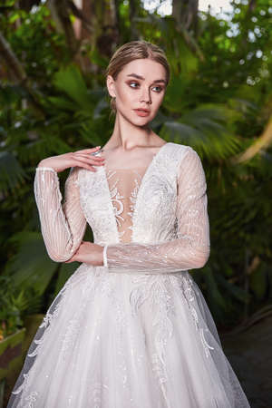 Beautiful sexy woman model bride wearing white long silk and lace wedding dress fashion espousal bright makeup blond hairstyle ceremony in green summer garden love.