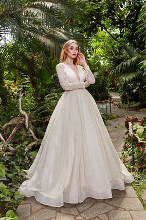 Beautiful woman model bride wearing white long silk and lace wedding dress fashion espousal bright makeup hairstyle blond ceremony in green summer garden love.