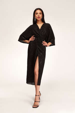 Sexy pretty woman tanned skin long brunette dark hair bright makeup wear fashion party style sequins midi black dress for meeting date celebration evening high heels shoes glamor lifestyle luxury.