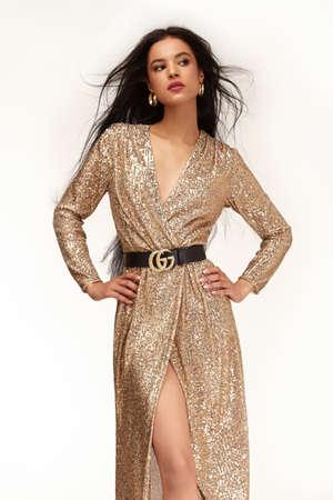 Pretty sexy beautiful woman long brunette dark hair glamor luxury life style wear gold midi long dress style for party date celebration evening accessory jewelry fashion designer clothes studio. 版權商用圖片