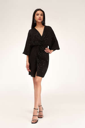 Sexy pretty woman tanned skin long brunette dark hair bright makeup wear fashion party style sequins little black dress for meeting date celebration evening high heels shoes glamor lifestyle luxury. 版權商用圖片