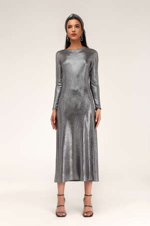 Fashion beautiful model glamor lifestyle sexy brunette woman wear clothes silver color midi dress shine bright high heels accessory jewelry party style date attractive studio background. 版權商用圖片