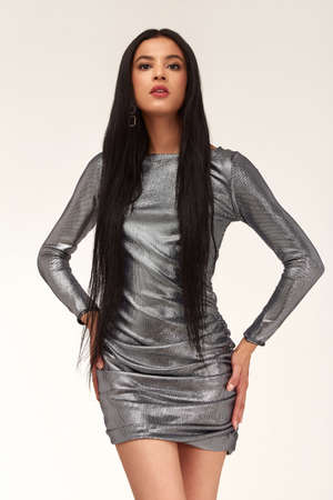 Fashion beautiful model glamor lifestyle sexy brunette woman wear clothes silver color dress short skinny shine bright high heels accessory jewelry party style date attractive studio background. 版權商用圖片
