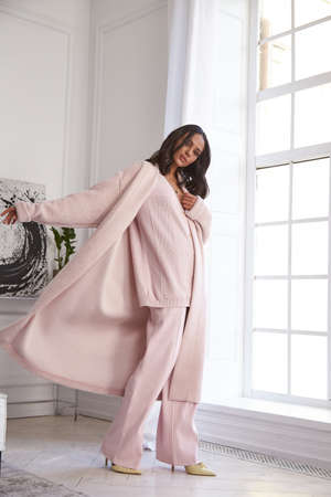 Pretty fashion beautiful woman sexy lady brunette curly hair dark tanned skin wear trend clothes knitted pink pink suit jacket top pants shoes interior room sofa plants spring collection luxury life. 版權商用圖片