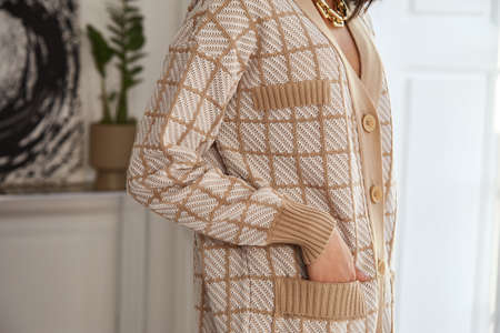 Pretty fashion beautiful woman sexy lady brunette curly hair dark tanned skin wear trend clothes knitted beige suit jacket top pants shoes interior room sofa plants spring collection luxury.