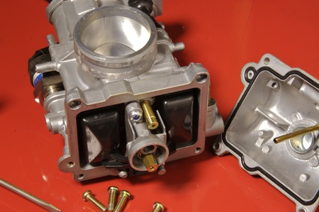 Four-stroke motorcycle carburetor with tools dissembled. photo