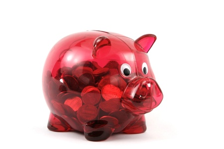 Transparent red piggy bank full on change
