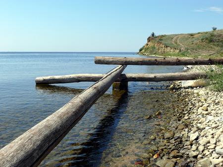 Beaches d logs rocks stones.Logs and stones on seacoast. Stock Photo