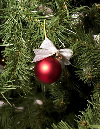 Fir-tree, decorated on Christmas. Artificial Fir-tree, red ball, bluebell. Stock Photo