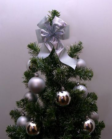 Christmas-tree, decorated to the holiday, in silvery tones.