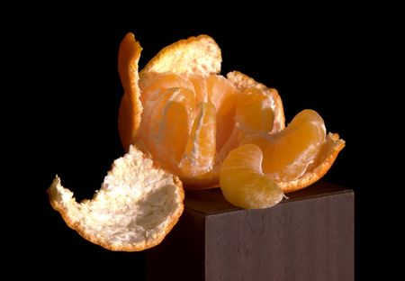 sours: Cleared mandarine on a black background. Stock Photo