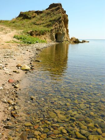Beach. Quiet, transparent water, rocks on the bottom. The high cliff away.