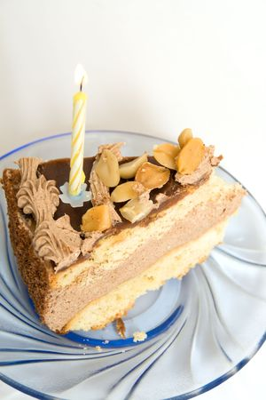 A piece of cake with candles on a glass saucer.