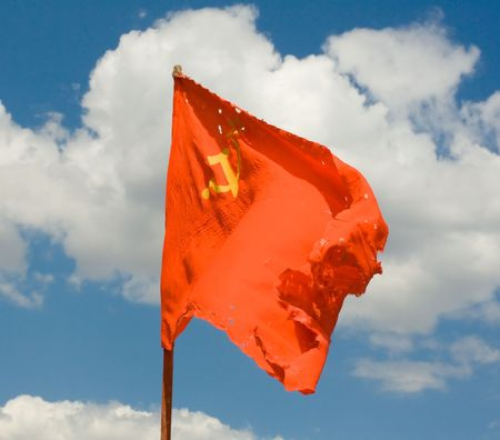 Torn, dirty, old Soviet red flag against the backdrop of the sky.