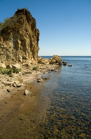 Sunny day at the beach desert. The sky, water, rocks, stones under water. Stock Photo