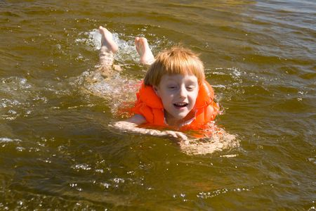 Little swimmer floating on the river. In life jacket.