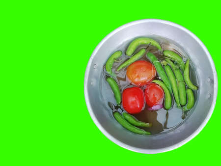 closeup view of tomatoes and green chili peppers in a bowl isolated on green background