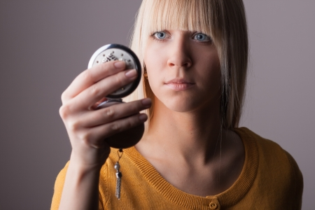 Young woman looking into a mirror Stock Photo - 17098282