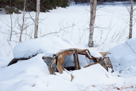 Abandoned car wreck in winter photo